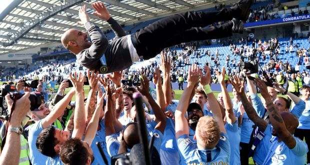 Guardiola being lifted up by Man City Players