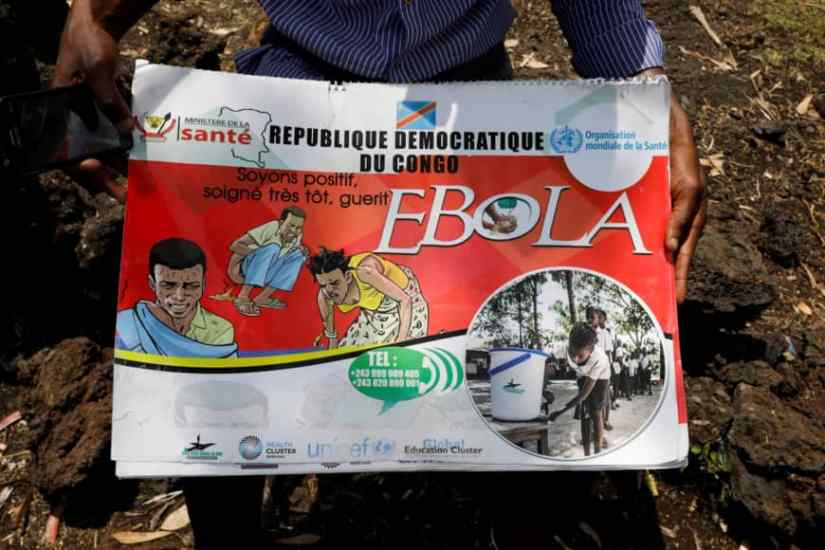 Congolese volunteer Ferdinand Tangenyi displays a flip book he uses to inform people about the Ebola virus, in Goma